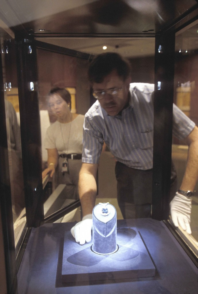 Photo: Photographed through the thick protective glass of the Hope Diamond's exhibition case, Jeffrey Post returns the diamond to its pedestal in the Harry Winston Gallery of The Janet Annenberg Hooker Hall of Geology, Gems, and Minerals in the Smithsonian's National Museum of Natural History. (Photos by Chip Clark)