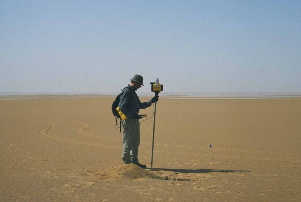 Geologist standing in a desert with a GPS device