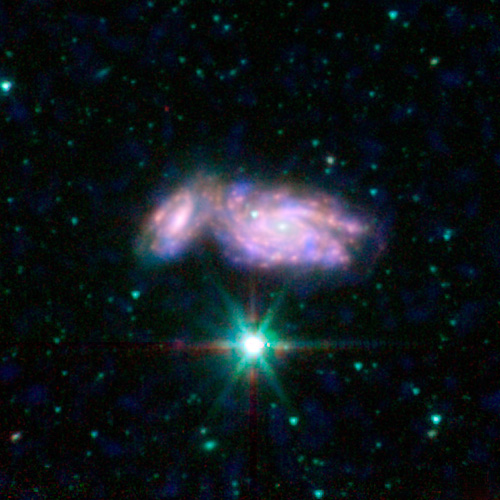 Three-color image of NGC 935 and its companion IC 1801 showing far-UV emission from young stars observed by GALEX in blue, heated dust mid-infrared emission observed by Spitzer in red, and stellar near-infrared emission observed by Spitzer in green. This pair of spiral galaxies is beginning to crash into each other. Credit: NASA / JPL-Caltech / L. Lanz (Harvard-Smithsonian CfA)