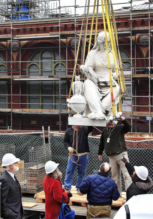 "The figure representing ""Science"" from the statue ""Columbia Protecting Science and Industry"" is gently lowered onto a truck. The entire statue was removed from above the north entrance of the Smithsonian's Arts and Industries Building in Washington, D.C. on Wednesday, Feb. 8, 2012, as the building undergoes renovation. The figure ""Science,"" is depicted reading a book with the owl of wisdom at her feet. The sculpture was done by New York sculptor Casper Burberl. (Photo by Eric Long)"