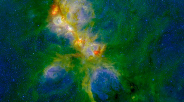 This representative-color photo of NGC 6334 combines infrared data from the Herschel and Spitzer spacecraft and ground-based NEWFIRM instrument. Warm dust, illuminated by the high-mass stars that are scattered throughout the cloud complex, shows up in green. The red and orange spots mark the very massive young stars that are just forming within the nebula. The dark clouds, primarily at the upper left and lower right of the image, mark the densest areas where the next generation of stars will form. The hazy blue-white regions mark where the light emitted by the hot young stars is reflected back to us by the remaining dust and gas. In this photo red shows light at a wavelength of 70 microns, green is 8 microns, and blue is 1.2 microns. (Credit: S. Willis (CfA); ESA/Herschel ; NASA/JPL-Caltech/SSC; CTIO/NOAO/AURA/NSF)