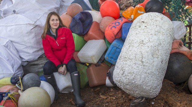 Odile Madden with a collection of plastic buoys, fishing floats and fuel containers found on the shore of Alaska's Blue Fox Island in 2013. The big white object on the right is a Japanese styrofoam buoy which break apart into smaller and smaller tiny individual balls. Animals peck at the fragments and can easily ingest them. Light weight and static prone, the styrofoam balls are very hard to clean up. (Photo (c) Kip Evans GYRE)