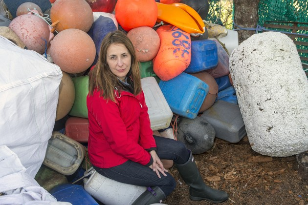 Odile Madden with a collection of plastic buoys, fishing floats and fuel containers found on the shore of Alaska's Blue Fox Island. The big white object on the right is a Japanese styrofoam buoy. Huge numbers of these styrofoam buoys have washed up on Alaskan shores since the 2011 tsunami, Madden says. The styrofoam buoys break apart, first into large fragments, and then smaller and smaller into tiny individual balls. Animals peck at the fragments and can easily ingest them. Light weight and static prone, the styrofoam balls are very hard to clean up. (Photo (c) Kip Evans GYRE)