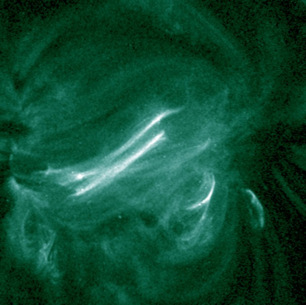 This image from the Atmospheric Imaging Assembly on board NASA's Solar Dynamics Observatory was taken simultaneously with the IRIS observations. It shows emission from hot coronal loops in a solar active region. IRIS observed brightenings occurring at the footpoints of these hot loops. The image is color-coded to show light at a wavelength of 94 Angstroms. The size of each pixel corresponds to about 430 km (270 miles) on the Sun. (NASA/SDO image)