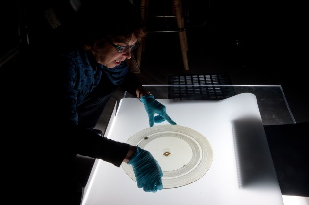 "National Museum of American History curator Carlene Stephens examines a glass disc recording containing the audio of a male voice repeating ""Mary had a little lamb"" twice, made more than 100 years ago in Alexander Graham Bell's Volta Lab. (Richard Strauss photo)"