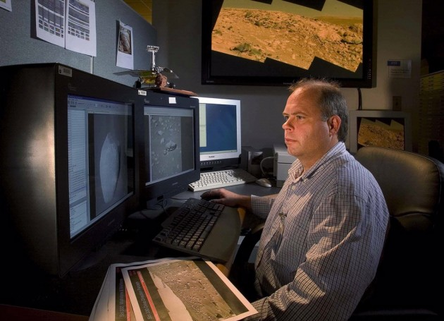 In his office at the National Air and Space Museum John Grant studies digital photographs taken by NASA rovers of the surface of Mars. (Photo by Eric Long)