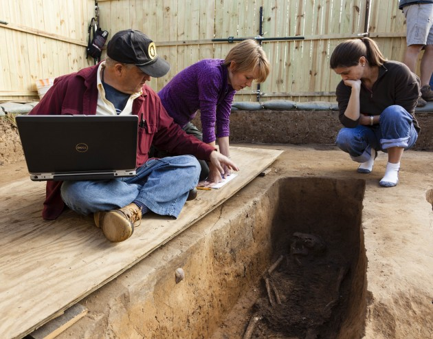 Smithsonian forensic anthropologists Doug Owsley and Kari Bruwelheide and colleague Ashley McKeown examine the grave of Rev. Robert Hunt. (Photo by Donald Hurlbert)
