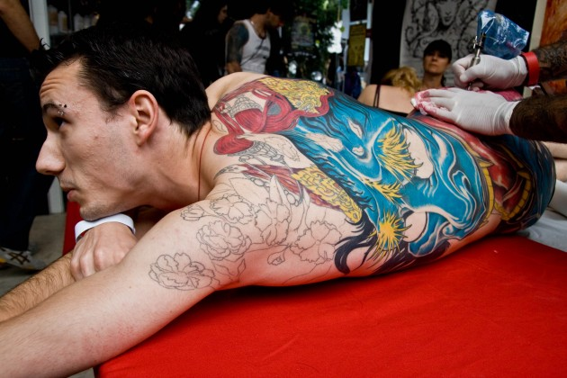 A man receives a colorful tattoo at a tattoo art fest in Paris (Flickr photo by Philleppe Leroyer)