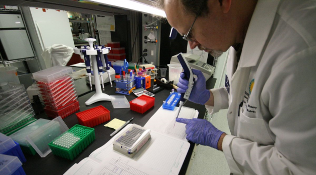 Dan Mulcahy, molecular laboratory technician at the Global Genome Initiative, processes genomic samples for DNA sequencing in a 10,000 square foot molecular lab in the National Museum of Natural History. (Image by Adrian Van Allen)