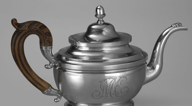 "Teapot made by Peter Bentzon, ca. 1817-1829, silver and wood, made in Philadelphia, Collection of the Smithsonian National Museum of African American History and Culture. The silver teapot has an oval vase-shape on a spreading pedestal foot, with curved spout capped by an incised patera and wooden leaf-capped scroll handle, and hinged domed cover with acorn finial. The scripted monogram ""MC"" has been engraved on the side and the name ""Rebecca Dawson"" has been engraved along the bottom rim."