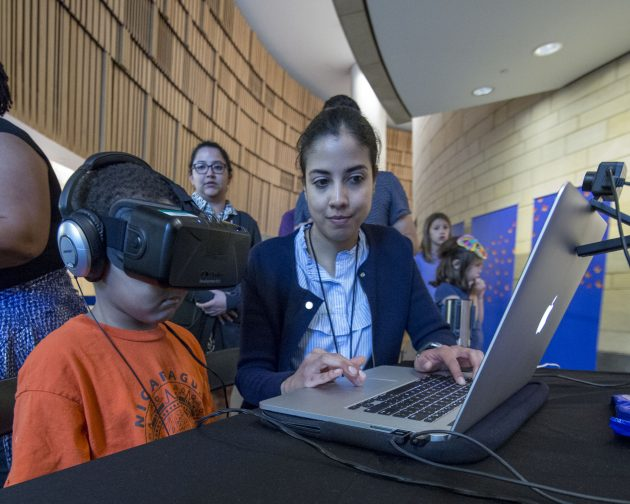 Child wearing virtual reality headset in front of laptop computer