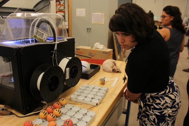 Woman looking at displays in front of 3D printer