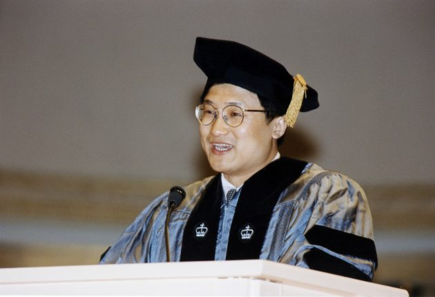 Li Lu in gown and mortar addresses graduation class