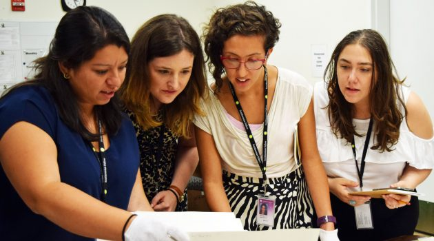 Stephanie Huezo, Maeve Coudrelle, Christina Azahar, and Shakti Castro (L to R) looking through recently acquired photographs at the Archives of the National Museum of American History. (Photo by Diana C. Bossa Bastidas)