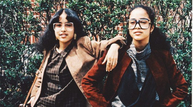 This color photograph shows identical twins wearing popular fashion from the 1980s in the East Flatbush section of Brooklyn, New York, in 1980. The girls are wearing oversized coats, skirts, shirts, and Cazal glasses. (Photo by Jamel Shabazz, courtesy National Museum of African American History and Culture)