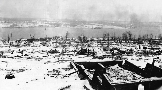 """A view across the devastated neighbourhood of Richmond in Halifax, Nova Scotia after the Halifax Explosion, looking toward the Dartmouth side of the harbour. The steamship Imo, one of the ships in the collision that triggered the explosion can be seen aground on the far side of the harbour – Halifax after 6th December 1917."" (Photo and caption Nova Scotia Archives and Records Management)"