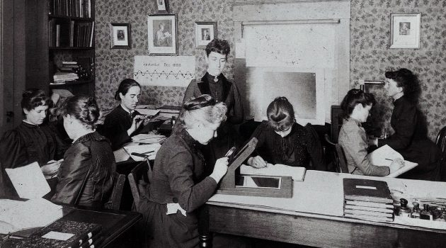 "Williamina Fleming (standing) supervises the team of women ""computers"" at the Harvard College Observatory as they help map the universe – one star at a time. (Harvard-Smithsonian Center for Astrophysics, Glass Plate Collection)"