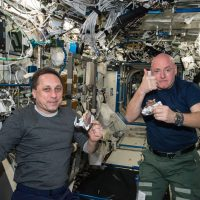 """NASA astronaut Scott Kelly gives the """"high sign"""" on the quality of his snack while taking a break from his work schedule aboard the International Space Station on Apr. 20, 2015. Russian cosmonaut Anton Shkaplerov (ROSCOSMOS) seems to agree on the tasty factor of the specially prepared space food. (Photo courtesy NASA)"""