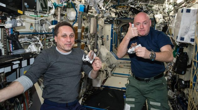 "NASA astronaut Scott Kelly gives the ""high sign"" on the quality of his snack while taking a break from his work schedule aboard the International Space Station on Apr. 20, 2015. Russian cosmonaut Anton Shkaplerov (ROSCOSMOS) seems to agree on the tasty factor of the specially prepared space food. (Photo courtesy NASA)"